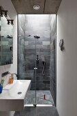Schmales, modernes Bad, seitlich Waschbecken mit Wandarmatur, im Hintergrund bodenebener Duschbereich mit gefliesten Wänden aus Schieferplatten