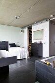 Schlafzimmer mit Sichtbetondecke und Schieferboden, im Vordergrund teilweise sichtbarer, offener Badbereich