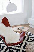 Butterfly Chair und Tabletttisch auf grafisch gemustertem schwarz- weissem Teppich