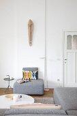 Graues Sofaelement mit grafischem Retromuster Kissen und Holzskulptur an Wand