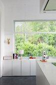 Weisse Küchenunterschränke vor Fenster mit Gartenblick