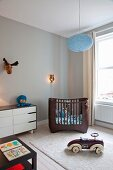 Weiße Retro Kommode, dunkelbraunes modernes Gitterbett und Spielauto im Kinderzimmer