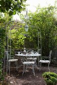 Ornate metal chairs and table under metal pergola in idyllic garden