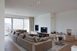 Edle minimalistische Stadtwohnung mit beigefarbener Couchlandschaft, offenem Kamin und maßgefertigtem Lowboard