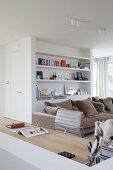 Gemütliche Loungeecke mit beigefarbenem Polstersofa, weißer Regalwand und integriertem Schreibplatz