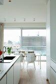 Blick von offener Küche auf hellen Esstisch mit Designerstühlen vor Fensterfront