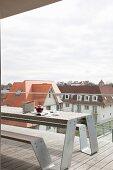 Moderner Terrassenplatz mit Holzbelag, Glasbrüstung und Bank-Tisch-Kombination, Blick auf Nachbargebäude