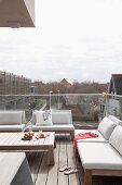 Dachterrasse mit Glasbrüstung und Outdoormöbeln mit hellen Polstern, Couchtisch
