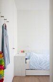 Weiß lackiertes Holzbett mit Schubladen und Bettkasten, Wandverkleidung und Einbauschrankwand