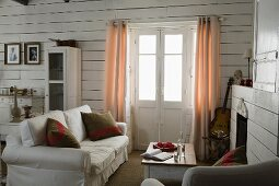 Sofa with scatter cushions next to French windows with curtains in corner of living room with white wood-clad walls