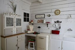 Retro dresser next to kitchen counter in corner of white, wood-clad kitchen