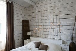 Simple bed with wooden headboard made of branches decorated with fairy lights against white, wood-clad wall