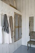Towels hanging on row of coat hooks next to fitted wardrobe with rustic louvre doors in white wood-clad partition