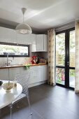 Designer chair at table next to white kitchen counter with French windows in background