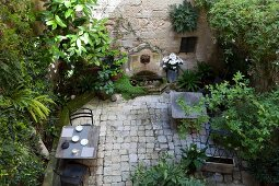 View down into planted courtyard with set table and chairs on paved floor