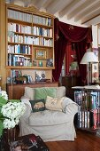 Bookcase, antique furniture, curtain on doorway and scatter cushions on armchair in classic living room