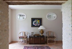 Open doorway in stone wall with view of wooden trunk between Scandinavian-style chairs below oval transom windows