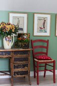 Red kitchen chair next to antique desk with bamboo frame below retro pictures on green wall