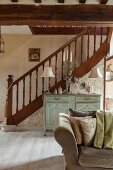 Turned staircase balustrade in open-plan, elegant, renovated interior with antique cabinet