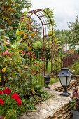 Metal trellis arch in summery, rustic garden with stone wall