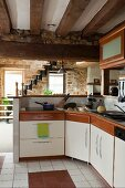 L-shaped kitchen worksurface with raised dining counter in front of staircase in interior with stone walls