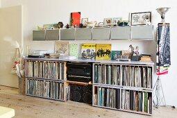 Offenes Sideboard mit Schallplatten Sammlung und HiFi-Anlage, oberhalb aufgehängte Kästen in Reihe
