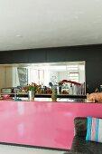 Kücheninsel mit pinkfarbener Front, im Hintergrund schwarzer Einbauschrank mit verspiegelter Wand in Nische