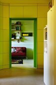 View from yellow hallway through green doorway into living area