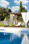 Wooden pergola with white curtains and wooden loungers with white cushions in summery garden
