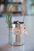 Tin can decorated with ribbon and test tube and used as biscuit tin