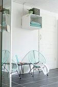 Turquoise retro cord chairs on grey-tiled floor below shelving module on wall