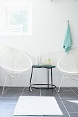 White cord chairs flanking black delicate side table and white bathmat on grey tiled floor