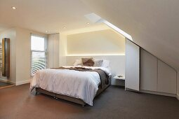 Upholstered bed in natural shades with indirect lighting in projecting masonry headboard and fitted wardrobe under sloping ceiling