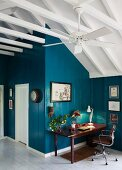Desk in corner of room with wood panelling painted petrol blue and exposed pavilion roof