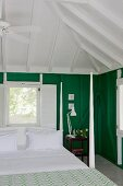 Bed with corner posts and snow-white bed linen below exposed pavilion roof structure, window with interior shutters and green-painted wooden walls