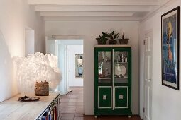Fluffy lampshade on maritime sideboard and glass-fronted crockery cabinet painted green and silver in hallway