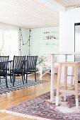 Offener Wohnraum mit Holzdecke, vorne teilweise sichtbare Theke und Holz Barhocker, im Hintergrund schwarze Stühle an Esstisch