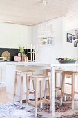 White modern breakfast bar and wooden bar stools in open-plan kitchen