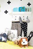 Stofftiere und Kissen mit Tiermotiven, vor an Wandkonsole aufgehängte Hosen, grafische Gestaltung an Wand
