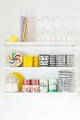 Schwarz-weisse Trinkbecher und Schalen, Konservendosen, Gläser und Strohhalme auf weißem Wandregal