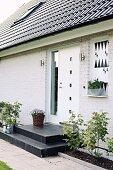 Wohnhaus mit geweisselter Ziegelfassade, vor weisser Haustür schwarze Podeststufen, seitlich schmale Beete