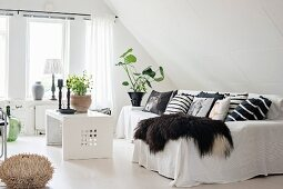 Animal-skin blanket, many scatter cushions and white throw on sofa and coffee table in lounge area in converted attic