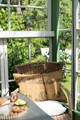Simple wicker chair with rustic cushions in corner of greenhouse