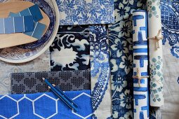 Wallpapers and fabrics in blue and white patterns and paint sample strips