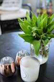 Glass vase of lily of the valley an tealight holders