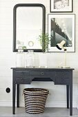 Black-painted console table, seagrass basket and pictures on wood-clad wall