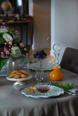 Pastries under glass cover and glass carafe of juice with spherical stopper on set table