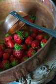 Fresh strawberries and ladle in copper bowl