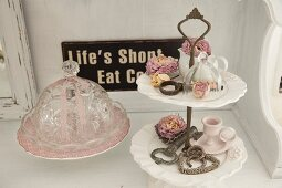 Crystal dish with cover, dried roses and shabby-chic ornaments on antique china cake stand and vintage sign on wall
