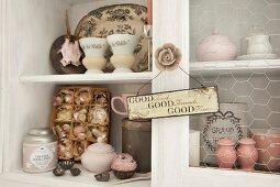 Pastellfarbenes Vintage Porzellan und Shabby Nippes in weisser Anrichte, Schild mit Sinnspruch an Griff in Rosenblütenform
